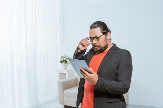 Entrepreneur concentrating while reading his tablet pc