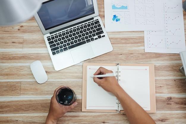 Предприниматель пьет стакан пресной воды и делает заметки в планировщике после анализа продаж, вид сверху