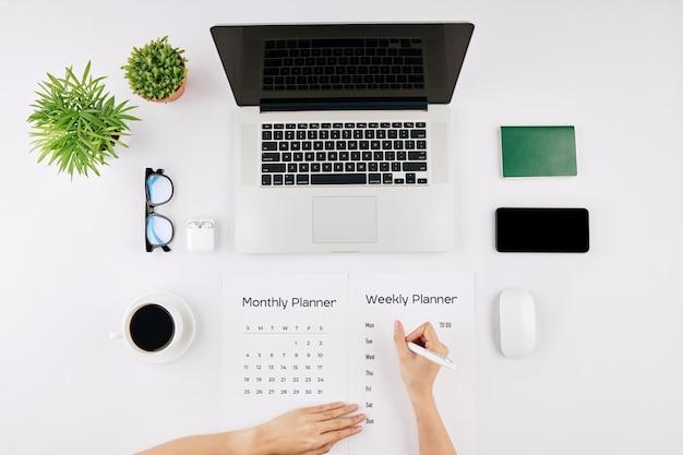 Entrepreneur filling weekhly planner