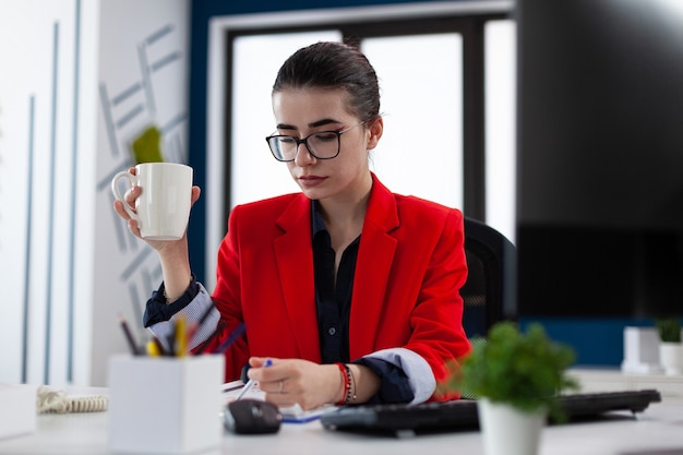 Предприниматель, держащий чашку кофе в офисе на рабочем месте