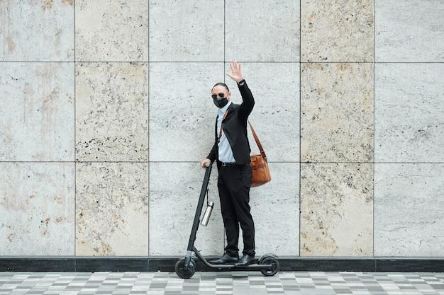 電動スクーターの上に立って手で手を振っている黒いスーツと保護マスクの起業家