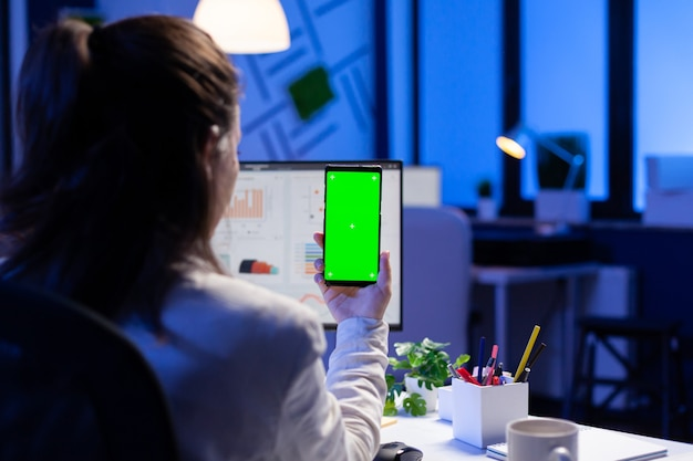 Entrepreneur looking at smartphone with green screen sitting at office desk overworking