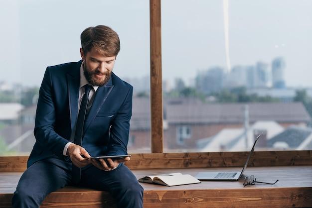ノートパソコンのオフィスを持つ窓の近くの起業家