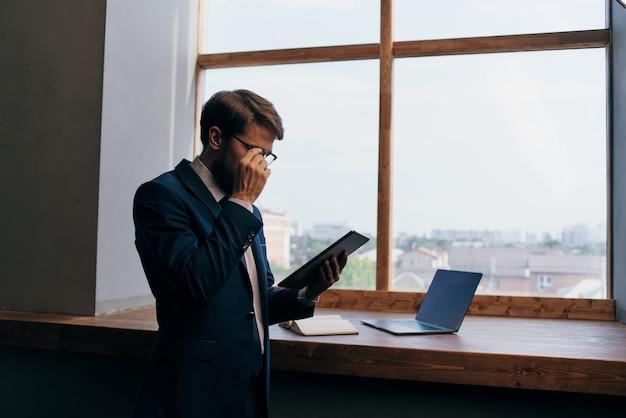 タブレットの自信を持って窓の近くの起業家