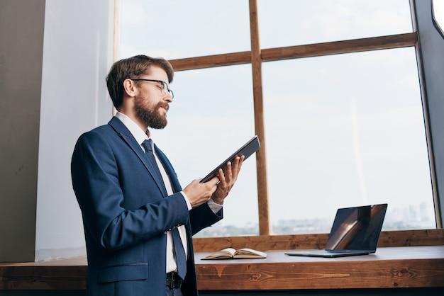タブレット技術を持つ窓の近くの起業家