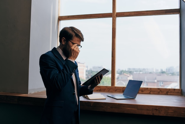 Entrepreneur near the window with a tablet selfconfidence