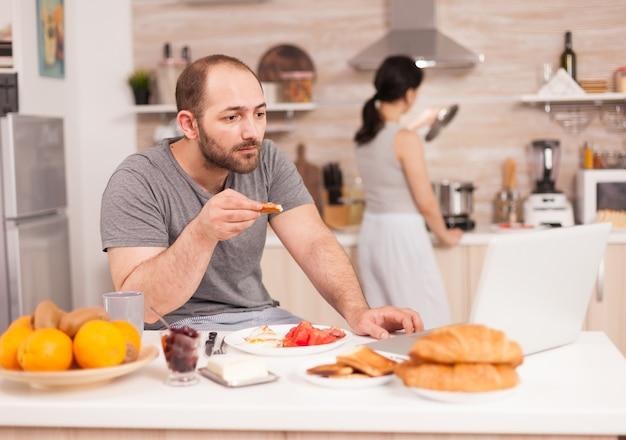 기업가는 부엌에서 아침을 먹으면서 화상 회의를 합니다. 원격으로 일하는 프리랜서, 집에서 화상 회의 화상 통화 온라인 웹 인터넷 회의, 통신 장치
