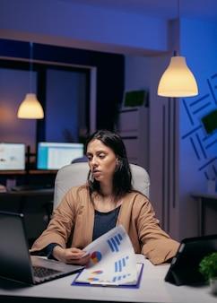 Imprenditore che cerca tra i documenti per completare una scadenza la sera. donna d'affari che fa gli straordinari in ufficio per finire un lavoro aziendale utilizzando tablet pc.