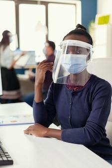 コロナウイルスに対するフェイスマスクを身に着けている彼女の職場に座っている起業家。世界的大流行の際の社会的距離を尊重する金融会社で働く多民族のビジネスチーム。