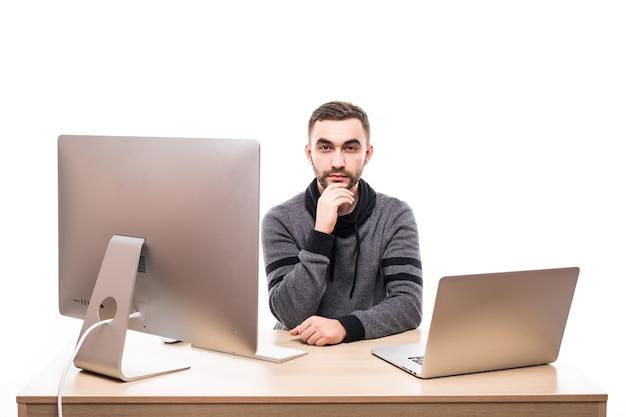 Предприниматель сидит за столом с ноутбуком и персональным компьютером и смотрит в камеру, изолированную на белом