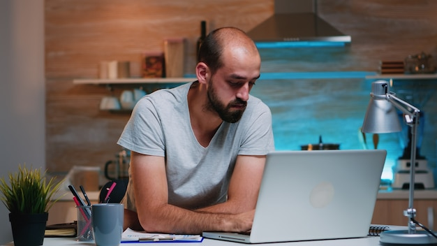 Entrepreneur sitting in remotely office working on laptop computer holding head with hands looking down. busy focused employee using modern technology network wireless doing overtime for job reading