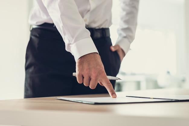 사무실 책상에 서 있는 기업가는 서명란에 대한 문서나 가입 양식을 가리키는 잉크 펜을 들고 있습니다.