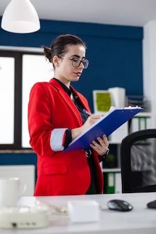 Entrepreneur standing in corporate office workplace taking notes on clipboard while doing financial analysis. manager filling paperwwork checking charts on computer screen.