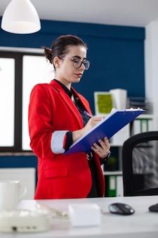 재무 분석을 하는 동안 클립보드에 메모를 하는 기업 사무실 직장에 서 있는 기업가. 관리자가 컴퓨터 화면에서 서류를 확인하는 차트를 작성합니다.