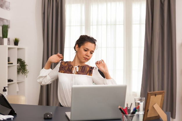 기업가는 홈 오피스에서 노트북 작업을 하는 동안 등을 스트레칭합니다.