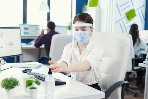 Covid-19로 전 세계적으로 유행하는 동안 손 위생을 위해 젤을 사용하여 안면 마스크와 안면 보호구를 착용하는 기업가. 동료들이 백그라운드에서 일하는 동안 소독하는 새로운 일반 직장의 사업가
