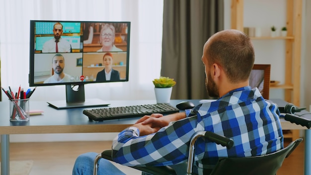 Entrepreneur in wheelchair communicating online with business partners.