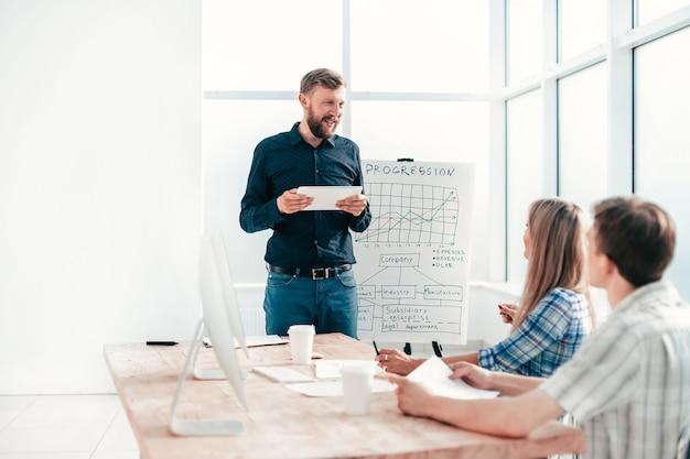 디지털 태블릿을 사용하는 기업가는 비즈니스 팀을 위해 보고서를 작성합니다. 팀워크의 개념