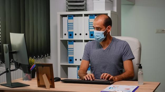 새로운 일반 직장에 앉아 컴퓨터에 마스크를 쓴 기업가. 코로나 바이러스에 대한 소독용 알코올 젤을 사용하여 손을 청소하는 현대적인 사무실 작업 공간에서 일하는 프리랜서