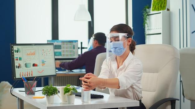 コンピューターで入力する前に、保護マスクとバイザーが手をこすりながら消毒ジェルを塗っている起業家。同僚がバックグラウンドで作業しながら消毒する新しい通常の職場の実業家