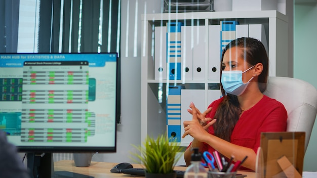 Предприниматель в защитной маске, проводящий видеовстречу, сидит в новом обычном офисе, соблюдая социальное дистанцирование. фрилансер, работающий на рабочем месте, общается с удаленной командой во время виртуального вебинара