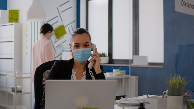 Entrepreneur with protective face mask discussing on landline while sitting at startup office desk in front of computer. caucasian female working at business meeting during coronavirus global pandemic