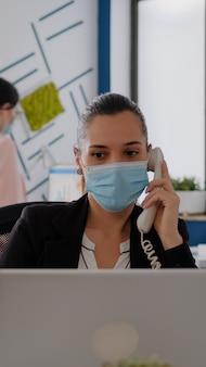 コンピューターの前のスタートアップオフィスの机に座って固定電話で話し合っている保護フェイスマスクを持つ起業家。コロナウイルスの世界的大流行の間にビジネス会議で働く白人女性