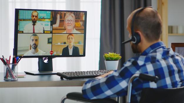 Предприниматель с инвалидностью при ходьбе в инвалидной коляске во время видеозвонка по бизнесу в интернете.