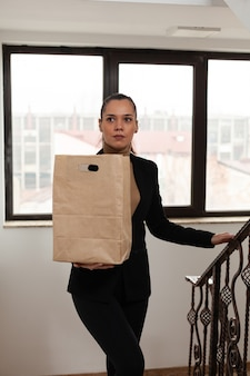 Entrepreneur woman climbing stairs in startup company office holding takeaway food meal order during takeout lunchtime