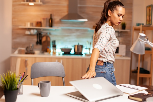 家で締め切り前にプロジェクトを終えた後、ラップトップを閉じる起業家の女性。深夜に最新のテクノロジーを使用して、仕事、ビジネス、忙しい、キャリア、ネットワーク、ライフスタイル、wiの残業をしている従業員