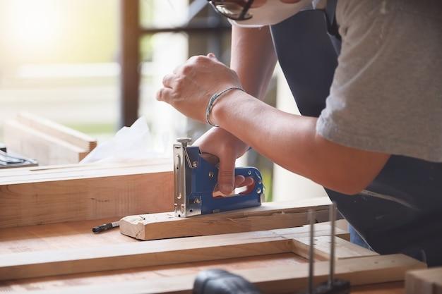 Предприниматель вудворк, владеющий степлером для сборки деревянных деталей по заказу клиента