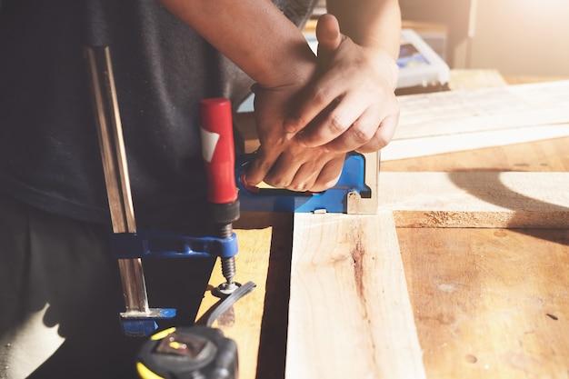 기업가 목공은 고객이 주문한 대로 나무 조각을 조립하기 위해 태커를 들고 있습니다.