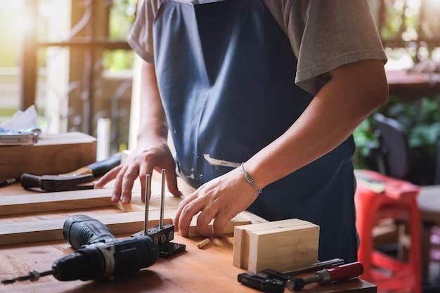 Предприниматель вудворк измеряет доски, чтобы собрать детали и построить деревянный стол для клиента.