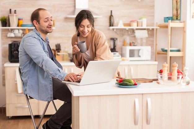 부엌에서 노트북 작업을 하는 기업가와 그의 일을 보고 있는 아내. 현대적인 wi-fi 무선 인터넷 기술을 사용하여 집에서 사랑하는 부부의 행복한 사랑의 쾌활한 낭만적인