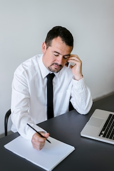 Entrepreneur working on the phone and writing notes sitting in a desk at office