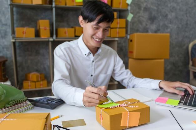 起業家の若い男は顧客情報を取っています。配送と配達