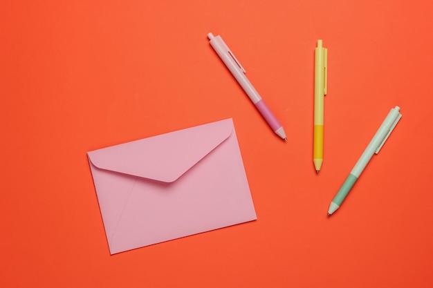 Конверт и цветные ручки на оранжевом фоне. вид сверху