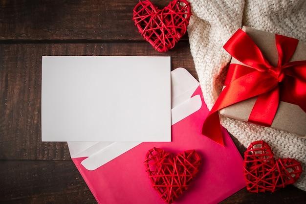 Конверт и поздравительная открытка на деревянном на день валентинок.
