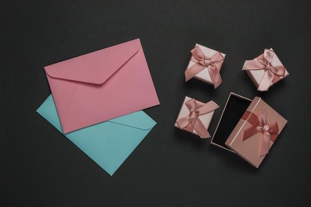 봉투, 검은 배경에 선물 상자입니다. 크리스마스, 발렌타인 데이, 결혼식 또는 생일. 평면도
