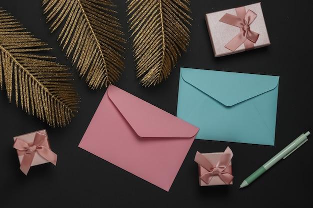 봉투, 황금 종려 잎 검은 배경에 선물 상자. 크리스마스, 발렌타인 데이, 결혼식 또는 생일. 평면도