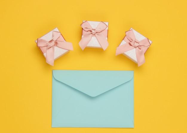 봉투, 노란색 배경에 선물 상자입니다. 크리스마스, 발렌타인 데이, 생일. 평면도