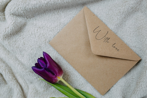Envelope of craft paper and one purple tulip on beige plaid, envelope with love, mail envelope.