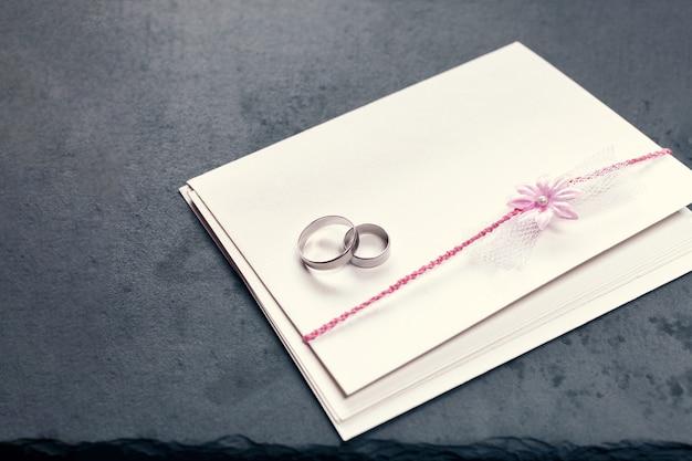 검은 배경에 분홍색 꽃과 두 개의 결혼 반지로 장식된 봉투