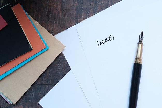 Конверт, пустая бумага и перьевая ручка на столе