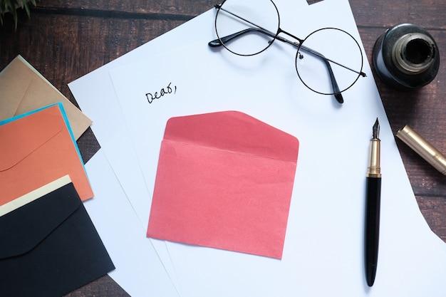 Конверт, пустая бумага и перьевая ручка на столе.