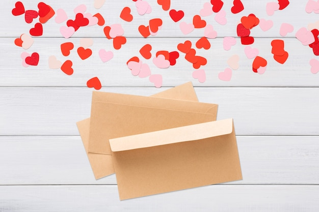 Envelope from craft paper with red heart on it, on white wood