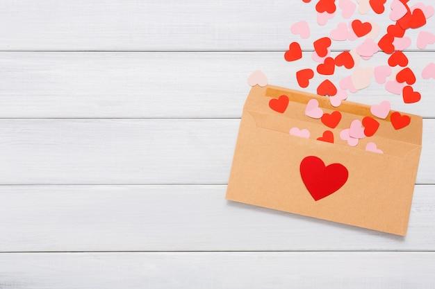 Конверт из крафт-бумаги с кучей красных сердечек на белом дереве