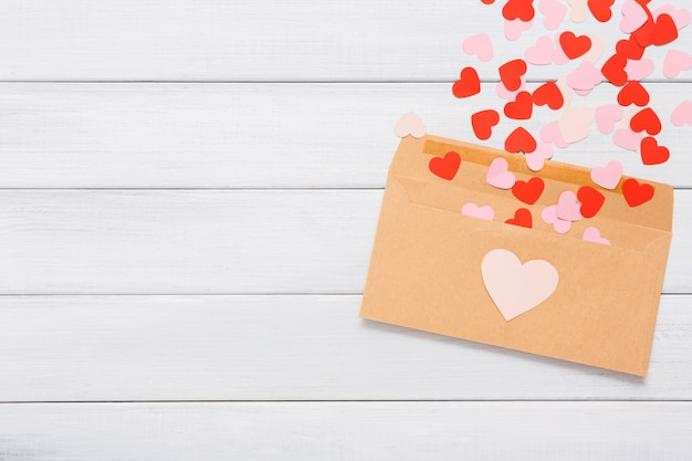 Envelope from craft paper with red hearts heap spread on white wood