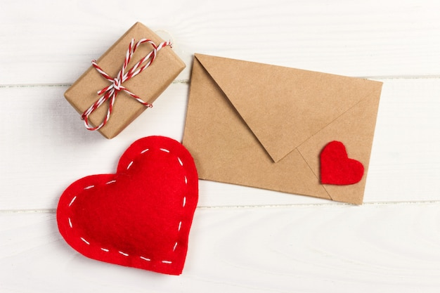 Envelope mail with red heart and gift box over white wooden background
