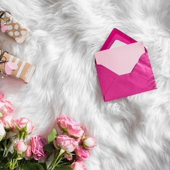 모직 둘러 앉아에 선물과 신선한 꽃 근처 봉투